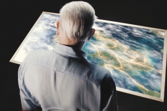 Sir David Attenborough looking at a map